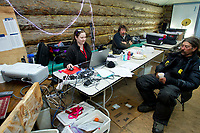 Comms volunteer Molly Farr works the computer and phones at Grayling on Saturday as race judge Art Church and musher Mike Santos hang out during Iditarod 2011