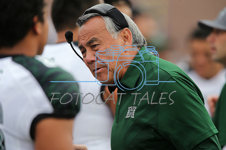 Hawaii head coach watches on the sidelines while his team plays against Nevada during the first half of an NCAA college football game in Reno, Nev., on Saturday, Oct. 24, 2015. (AP Photo/Cathleen Allison)