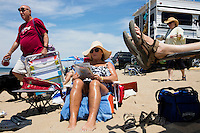 Donna Wells (in hat) and Dana Wells (feet at right), of Manchester, NH, sit on the beach at Herring Cove Beach in the Cape Cod National Seashore outside of Provincetown, Mass., USA, on Fri., July 1, 2016. Portions of the parking lot have been closed after land eroded during storms earlier this year. The couple estimate they have been coming to this beach for 20 years. In the past, they've taken an RV to the parking lot to sit near it, but this year, due to damage to the parking lot preventing RVs from parking, they had to park in a separate area and walk to the beach.