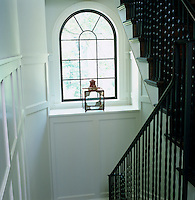 View down the wood panelled black and white staircase hall which has an arched window