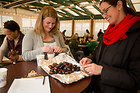 Friends of the Wissahickon Outreach Coordinator Sarah Marley (left) and Executive Director Maura McCarthey enjoy some fire-roasted chestnuts at the Winter in the Wissahickon event hosted by the Friends of the Wissahickon. (Dave Tavani/for NewsWorks)