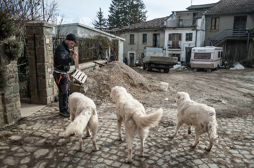 Santa Giusta, Italy, February 13, 2017. A man with his dogs at the village of Santa Giusta, hamlet of Amatrice, central Italy. Six months after the earthquake, nothing has changed. The rubble is still there; nothing has been moved, recorded or stored. People are still living in provisional accommodation but the greatest loss, to many residents, is the loss of their former peaceful lives.