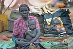 Angelina Awen sits with her granddaughter Aok in a camp for over 5,000 internally displaced persons in an Episcopal Church compound in Wau, South Sudan. Most of the families here were displaced by violence early in 2017, after a larger number took refuge in other church sites when widespread armed conflict engulfed Wau in June 2016. <br /> <br /> As the rainy season approaches, they have no shelter, and sleep every night in the open.<br /> <br /> Norwegian Church Aid, a member of the ACT Alliance, has provided relief supplies to the displaced in Wau, and has supported the South Sudan Council of Churches as it has struggled to mediate the conflict in Wau.