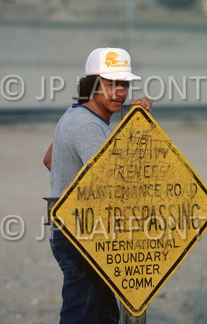 January, 1983. Tijuana, Mexico. A Mexican man stands next to a U.S., Mexico border sign, waiting for a chance to pass into the U.S.