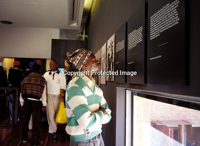 digasow00002 .South African Places. Gauteng. Soweto. An unidentified man looking at displays in the newly opened Hector Peterson museum on June 14, 2002 in Soweto, South Africa. Hector Peterson was killed during the student uprising in Soweto in 1976, where black students demonstrated against the Afrikaans language imposed by them by the Apartheid government. The new museum opened on Youth Day June 17, 2002..©Per-Anders Pettersson/iAfrika Photos