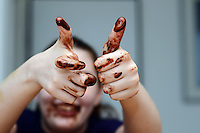 Girl with messy hands with chocolate. Like gesture