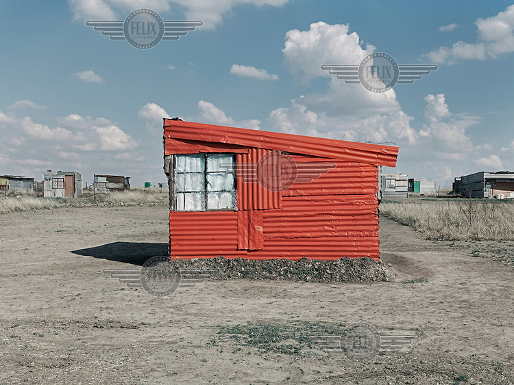 A corrugated iron shack neatly painted with red paint. Graeme Williams' pictures of the environments occupied by some of South Africa's poorest people focus on the interiors and exteriors of people's homes, accentuating the minutiae of the occupants' day-to-day dwelling places. The bright colours captured in these photographs are suggestive of resilience, hope and a sense of humanity that survives in these poverty-stricken communities...