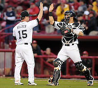 Relief pitcher Nolan Belcher (15) of the South Carolina Gamecocks high-fives his catcher, Dante Rosenberg (18) after completing the final out in a game against the Clemson Tigers on March 3, 2012, at Carolina Stadium in Columbia, South Carolina. South Carolina won, 9-6 and Belcher got the save. (Tom Priddy/Four Seam Images)