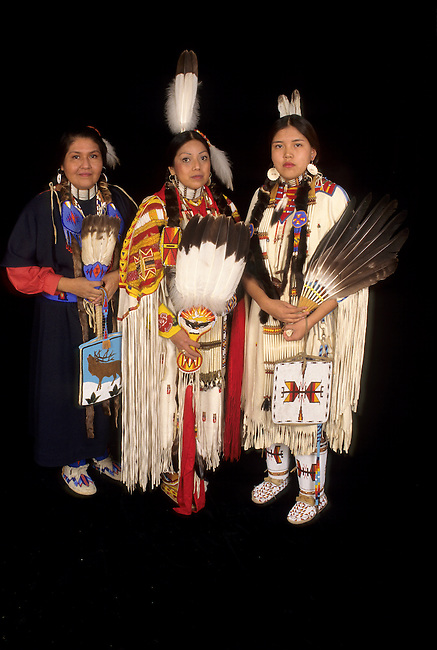 Native American family of mother in a trade cloth dress with teenage daughter who is dressed in traditional regalia and a woman who is a sister and auntie.