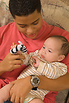 3 month old baby boy with 15 year old teenage brother, held, interested in toy puppet high contrast black and white  vertical Hispanic Puerto Rican