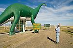 C. Fox photographs the wall Drug--80 foot green dinosaur at the dinosaur park along I-90