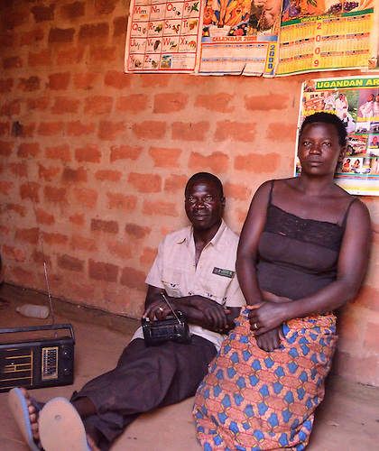 In northern Uganda,  a farmer and his wife relax in their new brick home.   The solid structure is an improvement over traditional mud huts.   In the remote region, radio is an important means of connecting with the outside.   The couple said they often listen to health messages.     After years of brutal insurgency by Joseph Kony's  Lords Liberation Army, the region is now peaceful, and recovering.  The couple and their children were forced to  live for many years during the insurgency in an armed government camp.