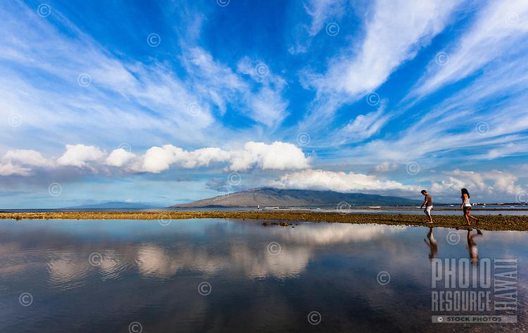 Happy couple walking around Koieie Fishpond in Kihei, Maui, with Lanai in the background.