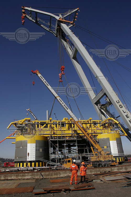 Main structures for the Ormen Lange gas field rolled out and assembled for the first time. Well templates rolled out of the assembly halls and down to the quayside, where the floating crane Uglen lifts the manifolds into place. ©Fredrik Naumann/Felix Features