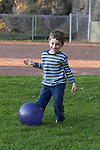 Berkeley CA Boy, five, happily playing with substitute soccer ball in park  MR