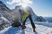 Female hiker uses shovel to clear ledge for tent on narrow mountain ridge, Moskenesøy, Lofoten Islands, Norway