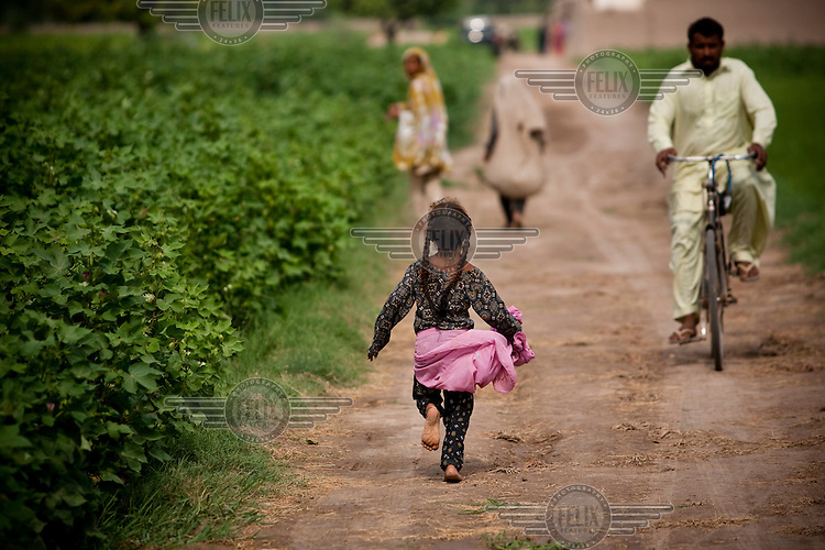 A young girl runs along a dirt village road.