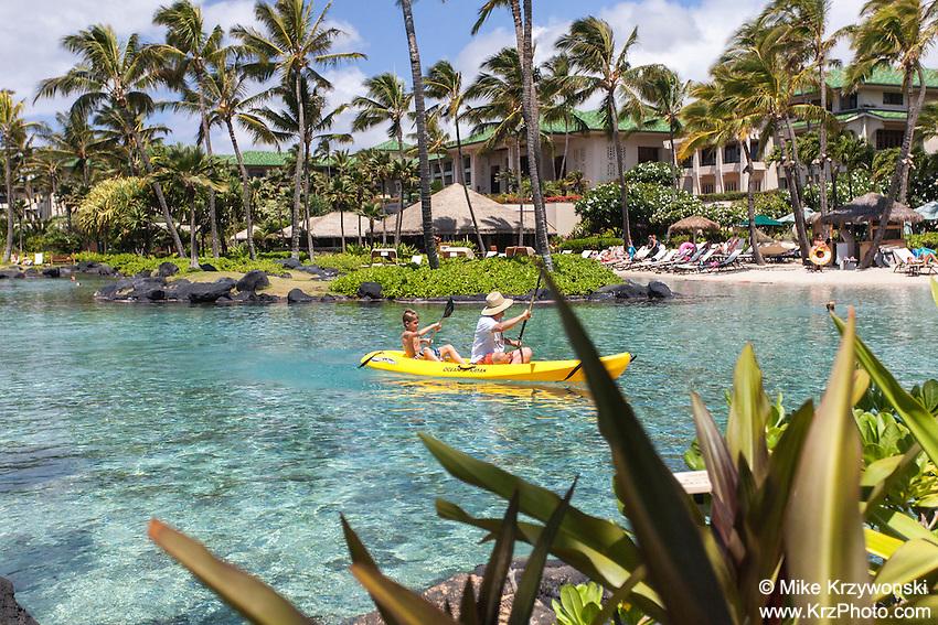 Caucasian man & boy kayaking in lagoon at at Grand Hyatt Kauai Resort in Koloa, Kauai