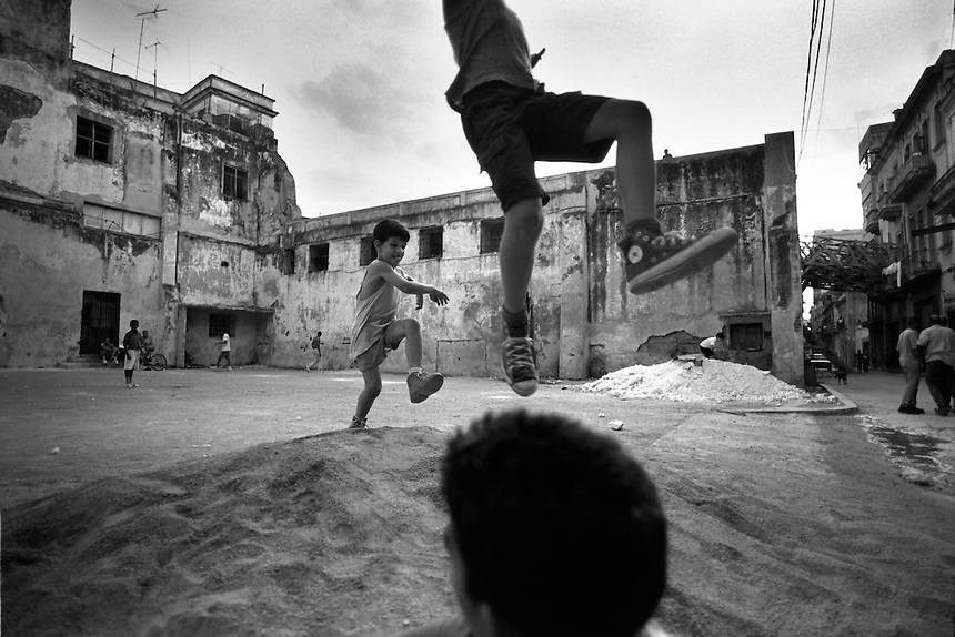 Young Habaneros make long jumps in a vacant lot in Old Havana.