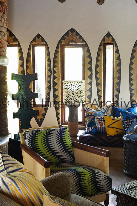 Seating with green patterned upholstery in a sitting area at the Singita Pamushana Lodge, Malilongwe Trust, Zimbabwe
