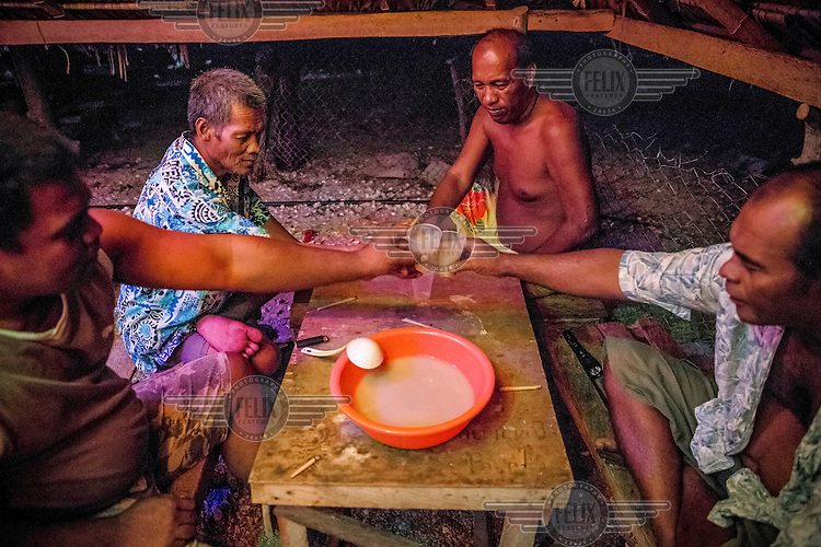 Elders of Taburao village drinking kava, a traditional drink derived from the kava plant that is a mild sedative of which varients are drunk throughout the Pacific region.