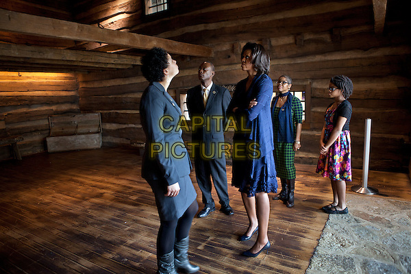First Lady Michelle Obama views The Slave Pen exhibit while touring the National Underground Railroad Freedom Center in Cincinnati, Ohio, February 23, 2012. Pictured, from left, are: Dina Bailey, Associate Curator of the National Underground Railroad Freedom Center; Cincinnati Mayor Mark Mallory; Verna Williams; and Allison Singleton.  .full length black blue grey gray suit dress arms crossed looking up.CAP/ADM/PS.©Pete Souza/CNP/AdMedia/Capital Pictures.