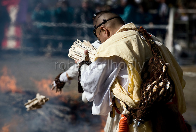 A novice priest bows and prays before throwing wooden prayer tablets on the flames of a bonfire during a purification ritual in which participants walk barefoot across burning embers in Takao, west of Tokyo, Japan on 14 March 2010.