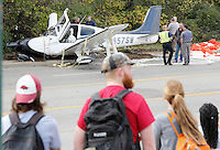 NWA Democrat-Gazette/DAVID GOTTSCHALK  Emergency responders secure the scene of a small airplane crash Tuesday, November 3, 2015, on Martin Luther King Boulevard in Fayetteville. Bill Simon, 56, Cliff Slincard, 59, and Maurice Willis, 47, were on the plane that deployed an emergency parachute attached to plane after an attempt at making an emergency landing at Drake Field in Fayetteville. The plane took off from Bentonville airport. All three men were transported to area hospitals with non life threatening injuries.