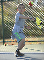 NWA Democrat-Gazette/ANDY SHUPE<br /> Pablo Lock, 7, of Fayetteville waits on a ball while playing tennis with father and sister at Wilson Park in Fayetteville. The trio decided to spend the day off from school at the park, taking advantage of the warm weather.
