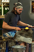 Glass artisan working with molten glass, Vermont, USA