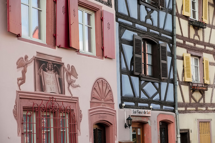 A mix of half timbered buildings with pastel stucco, shutters, and elaborate art work line the canal of the Petite Venise area in Colmar.