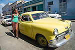 CIENFUEGOS, CUBA - DECEMBER 29: A Cuban woman with a vintage car parked in Cienfuegos, Cuba on December 29, 2013.  Prior to 2011, Cuban citizens could only purchase pre-revolution vehicles.
