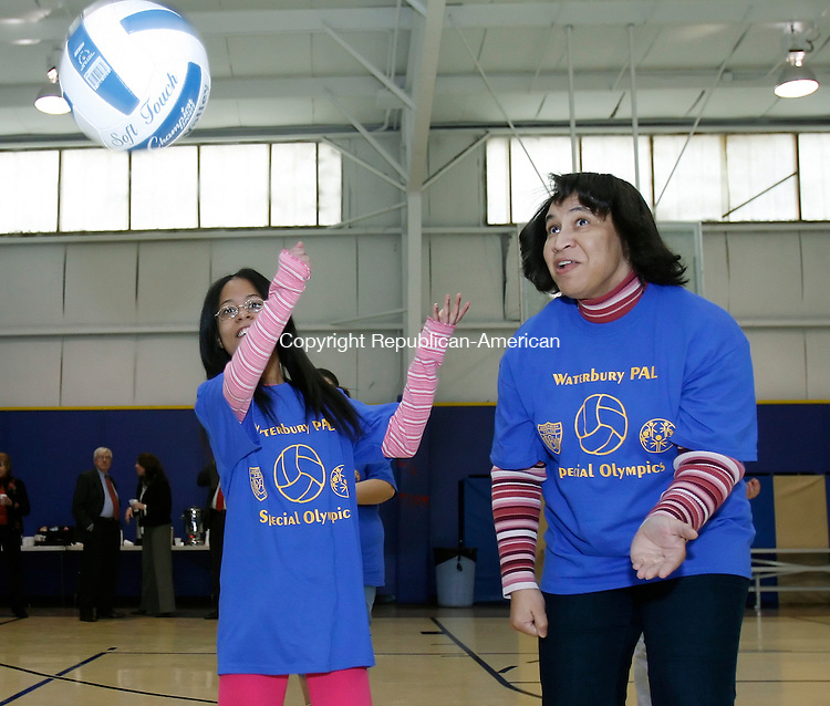 WATERBURY, CT, 01/20/09, 012009BZ02- Carla Cabrera, 13, serves a volleyball as volunteer Helen Taylor looks on during an exhibition game at the Waterbury Police Activities League (PAL) building on Division Street in Waterbury Tuesday.  PAL announced a partnership with Special Olympics earlier in the day.<br /> Jamison C. Bazinet Republican-American