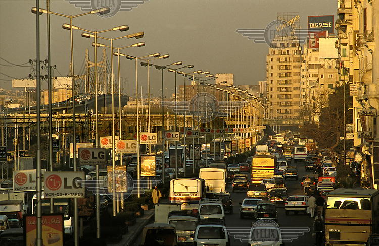 Rush hour traffic jam and advertising along Ramses Road at dusk, the air full of exhaust fumes..