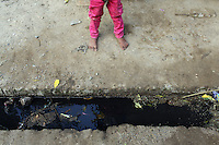 A child stands barefoot  next to a tainted water channel from a local leather producing tannery in Kanpur.