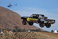 Dec. 18, 2009; Lake Elsinore, CA, USA; LOORRS unlimited light driver Brian Deegan takes a jump as a helicopter flies in the background during qualifying for the Lucas Oil Challenge Cup at the Lake Elsinore Motorsports Complex. Mandatory Credit: Mark J. Rebilas-US PRESSWIRE