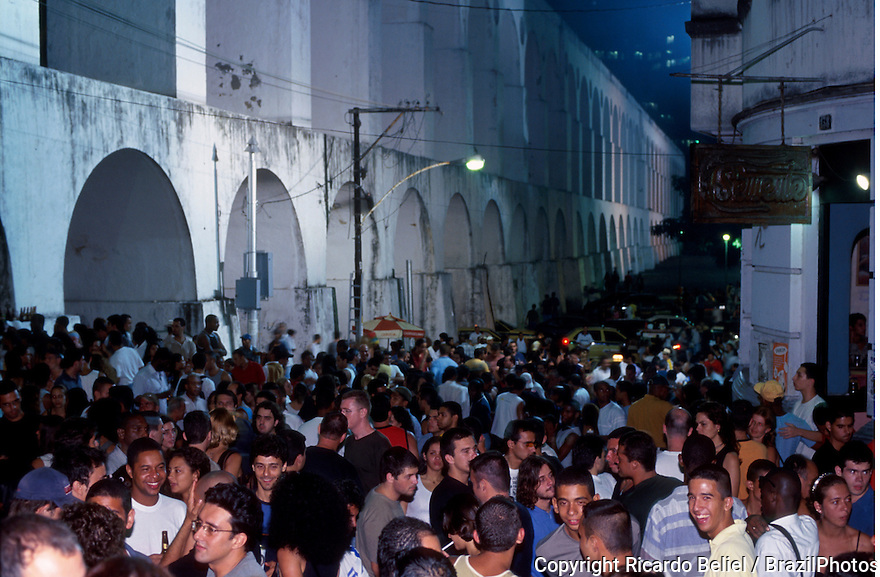 Young and multi-ethnic people enjoy nightlife at Lapa neighbourhood in Rio de Janeiro, Brazil besides Arcos da Lapa, an impressive aqueduct constructed in the mid-18th century by colonial authorities.
