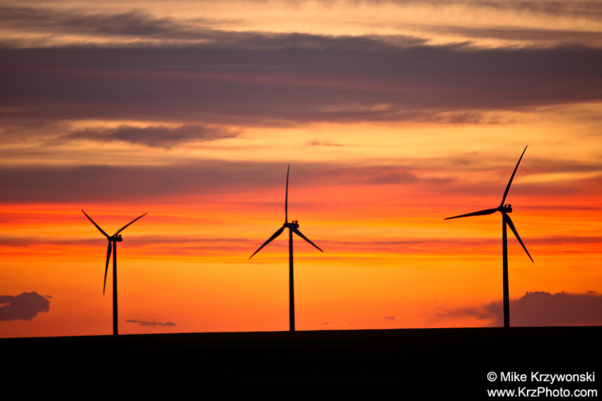Wind turbines against an orange sunset in Eastern Colorado