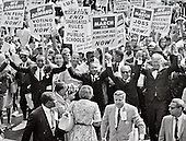 Reverend Dr. Martin Luther King, Jr and other civil rights leaders hold hands as they lead a crowd of hundreds of thousands at the March on Washington for Jobs and Freedom in Washington DC on August 28, 1963. From left to right: Roy Wilkins, Dr. King, Rabbi Joachim Prinz, unidentified. <br /> Credit: Arnie Sachs / CNP