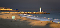 A thick marine layer provides a dark background for the last rays of sunlight on Seabright Beach and Walton Lighthouse in Santa Cruz, California.