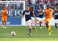 New England Revolution midfielder Diego Fagundez (14) brings the ball forward. In a Major League Soccer (MLS) match, the New England Revolution (blue/white) defeated Houston Dynamo (orange), 2-0, at Gillette Stadium on April 12, 2014.