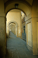 An early morning runner runs under  the Portico  of Lungarno degli Archibusieri in the  beautiful city of Florence .