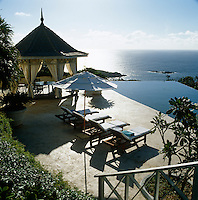 Sun-loungers are positioned in a row along one side of the infinity pool with a gazebo for dining overlooking the ocean