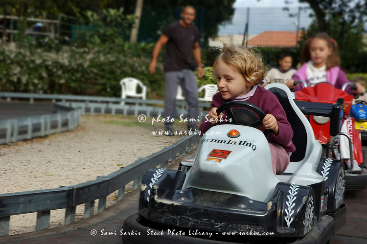 Four year old girl speeding in a go kart at an amusement park.