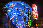 A man travels the Zip Line beneath the Fremont Street Experience neon display at night, Las Vegas, Nev..