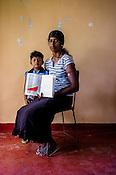 28 year old Kannathashan Saththiyavani poses for  photo with her daughter and the CHDR- Child Health Development Record Card (immunization/vaccination card) in Punaineeravi Village in Kilonochchi, Sri Lanka.  Photo: Sanjit Das/Panos
