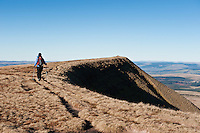 Female hiker hiking along summit ridge of Fan Brycheiniog in Black Mountain, Brecon Beacons national park, Wales