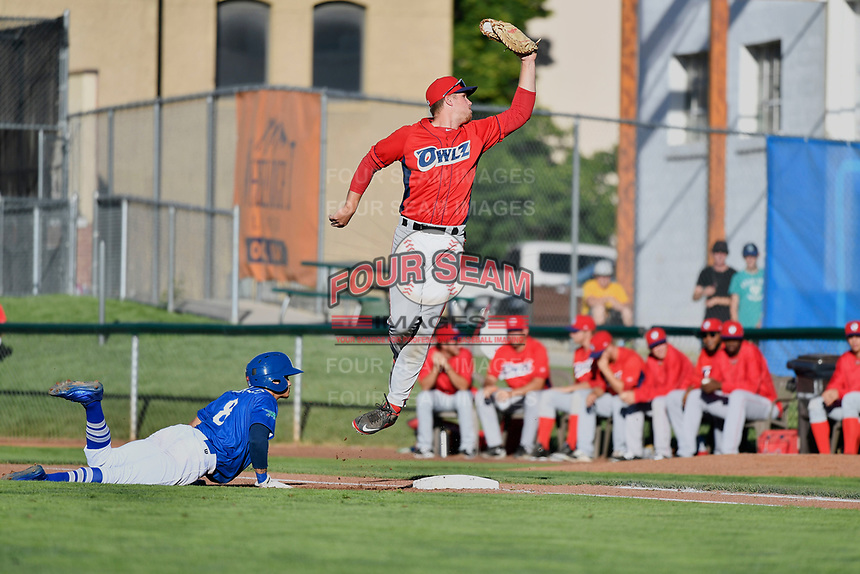 Brayan Morales (8) of the Ogden Raptors dives back to first base while Orem Owlz first baseman David MacKinnon (19) jumps for a high throw in Pioneer League action at Lindquist Field on June 22, 2017 in Ogden, Utah. The Owlz defeated the Raptors 13-8.  (Stephen Smith/Four Seam Images)