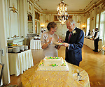 The wedding couple sharing cake cutting in the chandeliered ballroom of Sleepy Hollow Country Club.