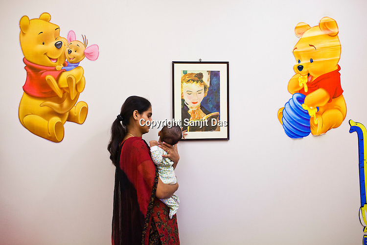 28 year old Veena Bhat takes a break from work and plays with her 4 month daughter, Aditi at the creche in Ernst & Young Global Shared Services office in Bangalore, Karnataka, India. Photo: Sanjit Das
